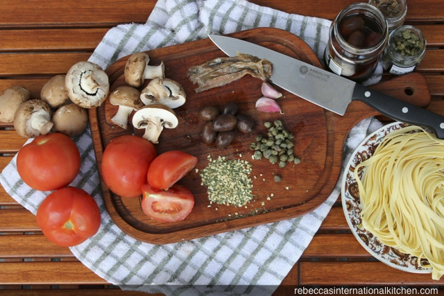 Ingredients for Pasta a la Putanesca: tomatoes, capers, olives, anchovies, and mushrooms